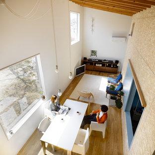 Esempio di un grande soggiorno minimalista aperto con sala della musica, pareti multicolore, pavimento in compensato, TV autoportante e pavimento marrone