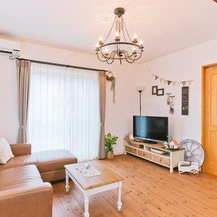 他の地域の地中海スタイルのおしゃれなファミリールーム (白い壁、無垢フローリング、据え置き型テレビ、茶色い床) の写真