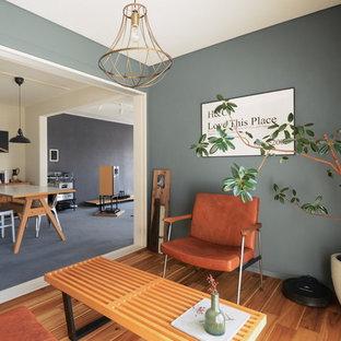 他の地域のインダストリアルスタイルのおしゃれなファミリールーム (グレーの壁、無垢フローリング、茶色い床) の写真