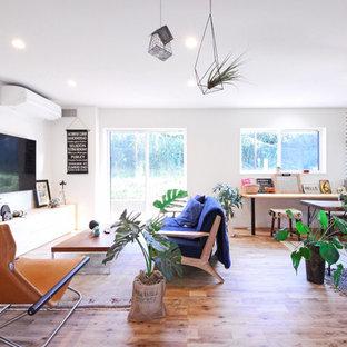 他の地域のインダストリアルスタイルのおしゃれなファミリールーム (白い壁、無垢フローリング、壁掛け型テレビ、茶色い床) の写真