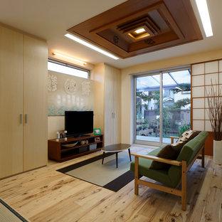 Imagen de sala de estar abierta, asiática, pequeña, sin chimenea, con suelo de madera clara, televisor independiente y paredes blancas