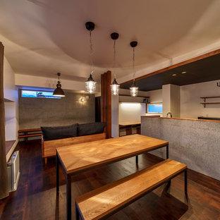 他の地域のインダストリアルスタイルのおしゃれなファミリールーム (マルチカラーの壁、濃色無垢フローリング、据え置き型テレビ、茶色い床) の写真