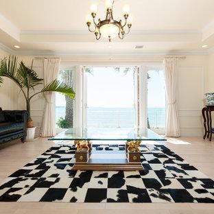 他の地域の地中海スタイルのおしゃれなファミリールーム (ベージュの壁、塗装フローリング、据え置き型テレビ、ベージュの床) の写真