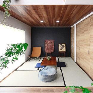他の地域のアジアンスタイルのおしゃれな独立型ファミリールーム (黒い壁、畳、緑の床) の写真