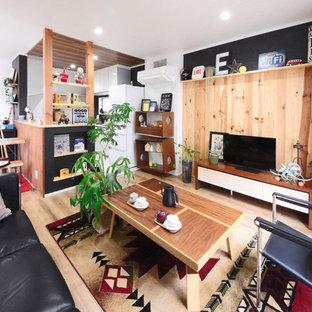 他の地域のインダストリアルスタイルのおしゃれなファミリールーム (マルチカラーの壁、淡色無垢フローリング、据え置き型テレビ、茶色い床) の写真