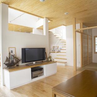 他の地域のアジアンスタイルのおしゃれなファミリールーム (白い壁、淡色無垢フローリング、据え置き型テレビ、茶色い床) の写真