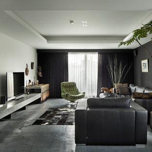 東京23区のコンテンポラリースタイルのおしゃれなファミリールーム (マルチカラーの壁、コンクリートの床、据え置き型テレビ、グレーの床) の写真