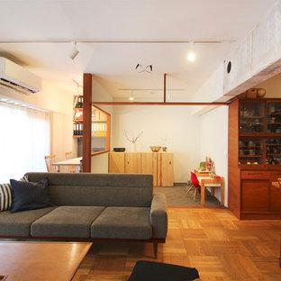 東京23区のアジアンスタイルのおしゃれなファミリールーム (白い壁、無垢フローリング、据え置き型テレビ、茶色い床) の写真