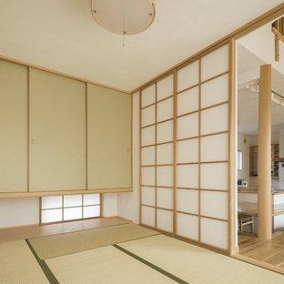 Modelo de sala de estar abierta, asiática, pequeña, sin chimenea y televisor, con paredes blancas, tatami y suelo verde