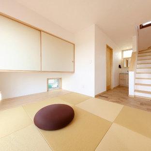 他の地域の地中海スタイルのおしゃれなファミリールーム (白い壁、畳、暖炉なし、緑の床、据え置き型テレビ) の写真