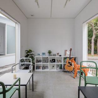 他の地域のコンテンポラリースタイルのおしゃれなファミリールーム (白い壁、コンクリートの床、グレーの床) の写真