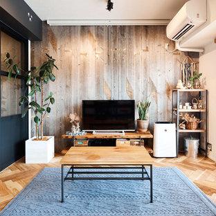 他の地域の北欧スタイルのおしゃれな独立型ファミリールーム (グレーの壁、無垢フローリング、据え置き型テレビ、茶色い床) の写真