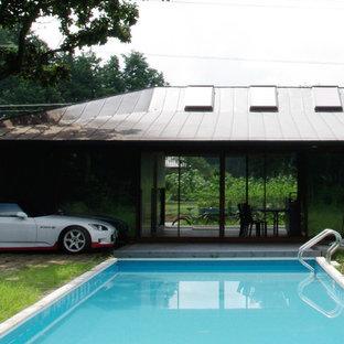 Ejemplo de casa de la piscina y piscina infinita, escandinava, rectangular, en patio trasero, con entablado