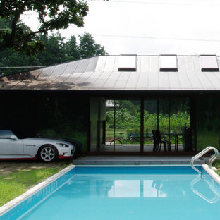 Inspiration for a scandinavian backyard rectangular infinity pool in Other with a pool house and decking.