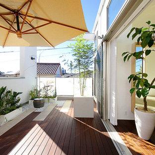 Immagine di terrazze e balconi etnici di medie dimensioni con un giardino in vaso e un parasole