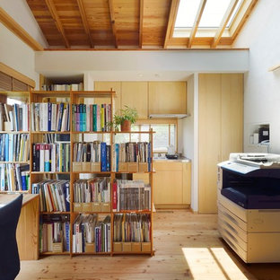 This is an example of a small rustic home studio in Tokyo Suburbs with white walls, medium hardwood flooring, a wood burning stove, a concrete fireplace surround, a freestanding desk and beige floors.