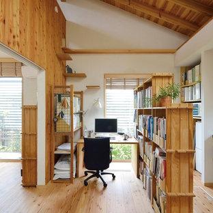 Ispirazione per un piccolo atelier stile rurale con pareti bianche, pavimento in legno massello medio, stufa a legna, cornice del camino in cemento, scrivania autoportante e pavimento beige