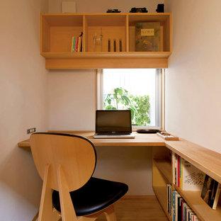 Стильный дизайн: маленькое рабочее место в скандинавском стиле с белыми стенами, встроенным рабочим столом и светлым паркетным полом - последний тренд