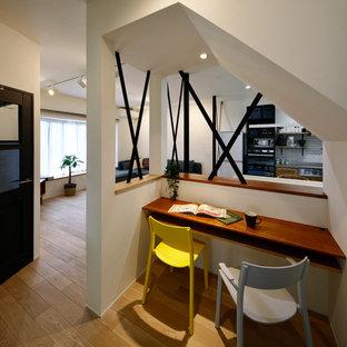 Idée de décoration pour un petit bureau nordique avec un mur blanc, un sol en bois brun, un bureau intégré et un sol marron.