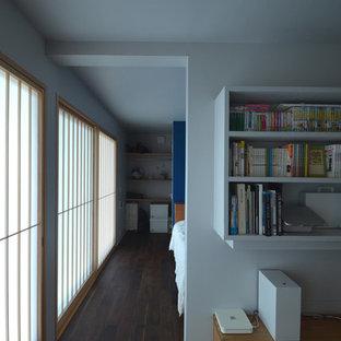 他の地域のモダンスタイルのおしゃれな書斎 (グレーの壁、合板フローリング、造り付け机、黒い床) の写真