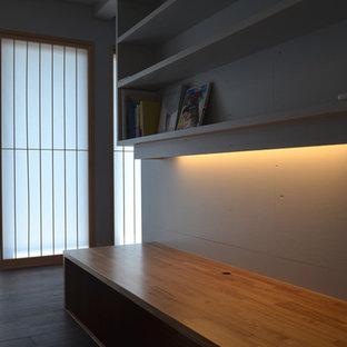 Idee per un ufficio moderno con pareti grigie, pavimento in compensato, scrivania incassata e pavimento nero