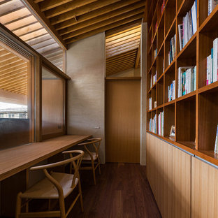 Réalisation d'un bureau asiatique avec un mur beige, un sol en contreplaqué et un bureau intégré.
