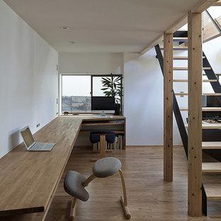 他の地域の北欧スタイルのおしゃれなホームオフィス・書斎 (白い壁、塗装フローリング、造り付け机、茶色い床) の写真