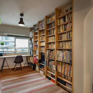 Idéer för mellanstora funkis hemmabibliotek, med vita väggar, mellanmörkt trägolv, ett fristående skrivbord och beiget golv