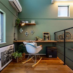 Mittelgroßes Arbeitszimmer mit Arbeitsplatz, grüner Wandfarbe, braunem Holzboden, Einbau-Schreibtisch, Tapetendecke und Tapetenwänden in Sonstige