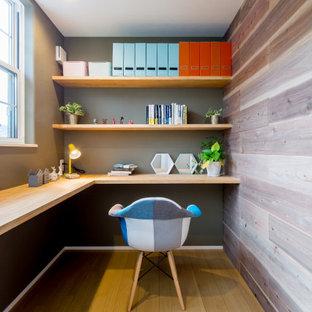 他の地域の中くらいのコンテンポラリースタイルのおしゃれな書斎 (板張り壁、グレーの壁、造り付け机、茶色い床) の写真