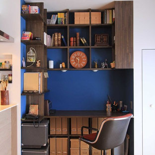 Example of a small asian built-in desk medium tone wood floor study room design in Nagoya with white walls
