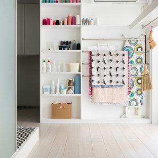 Imagen de estudio minimalista, pequeño, sin chimenea, con paredes blancas, suelo de contrachapado, escritorio independiente y suelo blanco