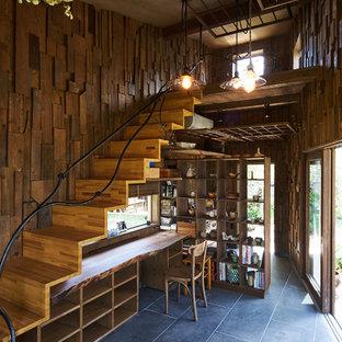 他の地域のラスティックスタイルのおしゃれなホームオフィス・書斎 (茶色い壁、造り付け机、黒い床) の写真