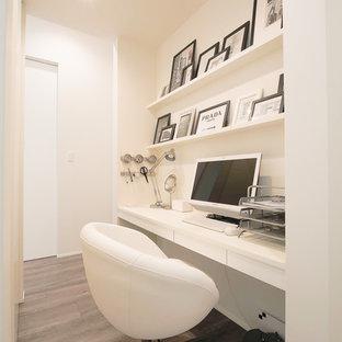 他の地域の小さいモダンスタイルのおしゃれなホームオフィス・書斎 (白い壁、塗装フローリング、造り付け机、グレーの床) の写真