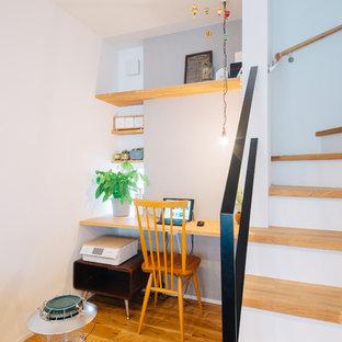 他の地域の北欧スタイルのおしゃれなホームオフィス・仕事部屋 (グレーの壁、無垢フローリング、暖炉なし、造り付け机、茶色い床) の写真