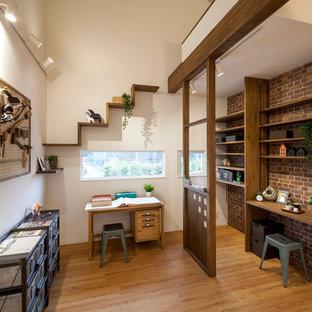 横浜のインダストリアルスタイルのおしゃれなホームオフィス・書斎 (マルチカラーの壁、無垢フローリング、自立型机、茶色い床) の写真