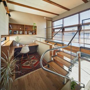 他の地域の広いアジアンスタイルのおしゃれな書斎 (白い壁、淡色無垢フローリング、造り付け机、茶色い床、表し梁、壁紙) の写真