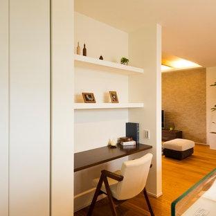 他の地域のアジアンスタイルのおしゃれなホームオフィス・仕事部屋 (白い壁、無垢フローリング、造り付け机、茶色い床) の写真