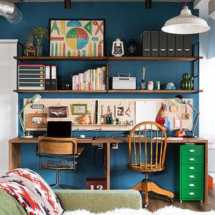 Aménagement d'un petit bureau industriel avec un mur bleu, un sol en contreplaqué, aucune cheminée, un bureau intégré et un sol marron.