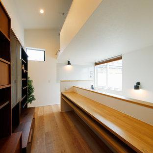 Idée de décoration pour un bureau nordique de taille moyenne avec un mur blanc, un sol en bois brun, un bureau intégré et un sol marron.