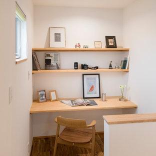 Modelo de despacho de estilo zen con paredes blancas, suelo de madera pintada, escritorio empotrado y suelo marrón