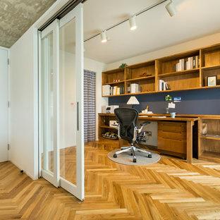 На фото: кабинет в скандинавском стиле с белыми стенами, паркетным полом среднего тона, встроенным рабочим столом и коричневым полом с