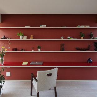 Immagine di uno studio scandinavo con pareti rosse, pavimento in legno verniciato, scrivania incassata e pavimento beige