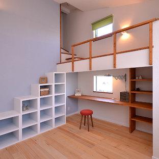 他の地域のコンテンポラリースタイルのおしゃれなホームオフィス・書斎 (青い壁、淡色無垢フローリング、造り付け机、茶色い床) の写真