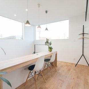 他の地域の小さいモダンスタイルのおしゃれなホームオフィス・書斎 (白い壁、淡色無垢フローリング、造り付け机、ベージュの床) の写真