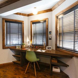 他の地域のコンテンポラリースタイルのおしゃれなホームオフィス・仕事部屋 (白い壁、塗装フローリング、造り付け机、茶色い床) の写真