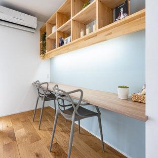 他の地域の中くらいのコンテンポラリースタイルのおしゃれな書斎 (青い壁、無垢フローリング、造り付け机、茶色い床) の写真