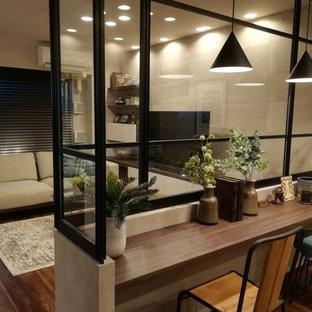 他の地域のインダストリアルスタイルのおしゃれなホームオフィス・書斎 (造り付け机、グレーの壁、合板フローリング、茶色い床) の写真