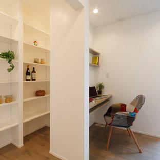 Inredning av ett arbetsrum, med ett bibliotek, vita väggar, ljust trägolv, ett inbyggt skrivbord och beiget golv