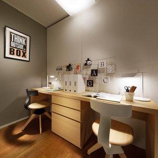 東京23区のコンテンポラリースタイルのおしゃれなホームオフィス・書斎 (グレーの壁、無垢フローリング、自立型机、茶色い床) の写真